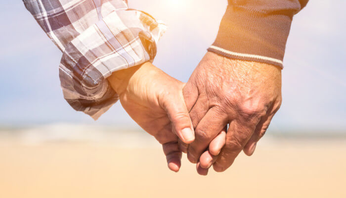 The hands of an older couple walking together