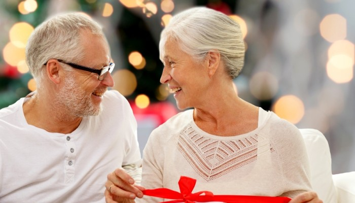 Older woman and man opening Christmas presents