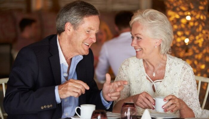 Older couple eating and talking in noisy cafe
