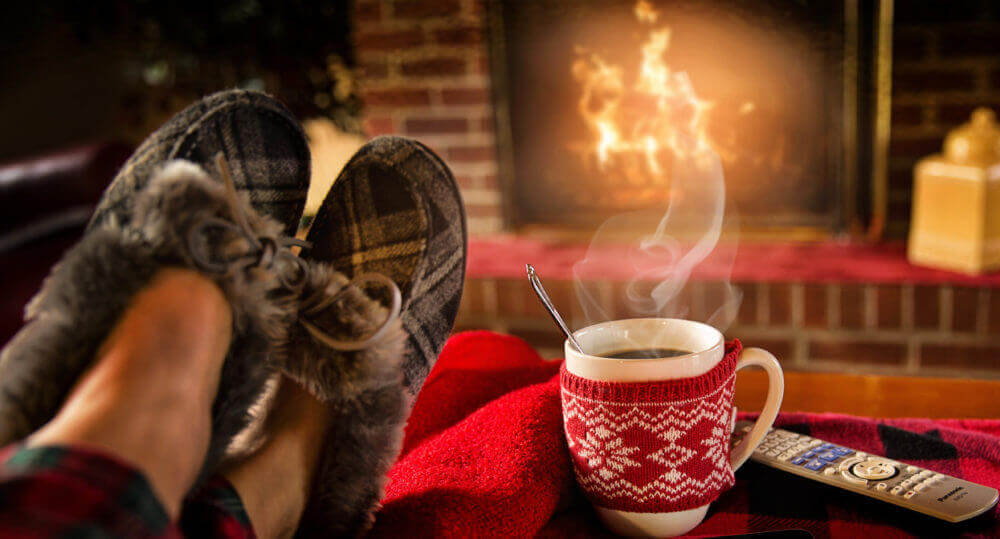 person with feet up in front of fire winter